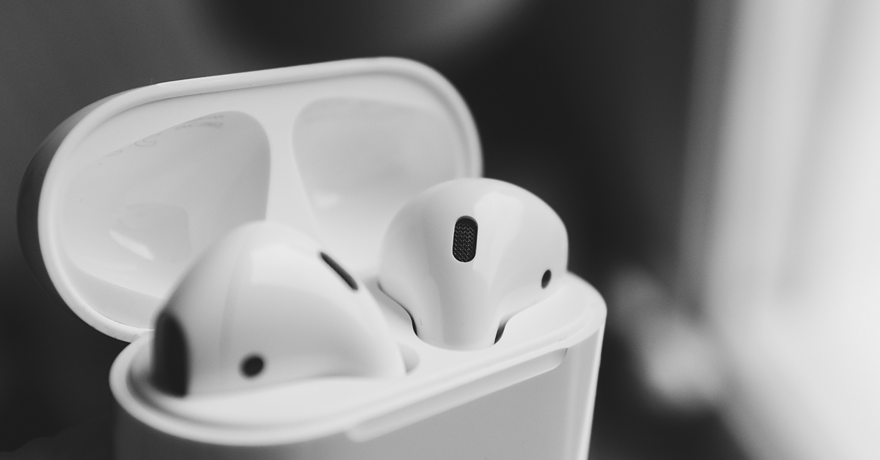 Apple AirPods tucked into the charging box with the lid open