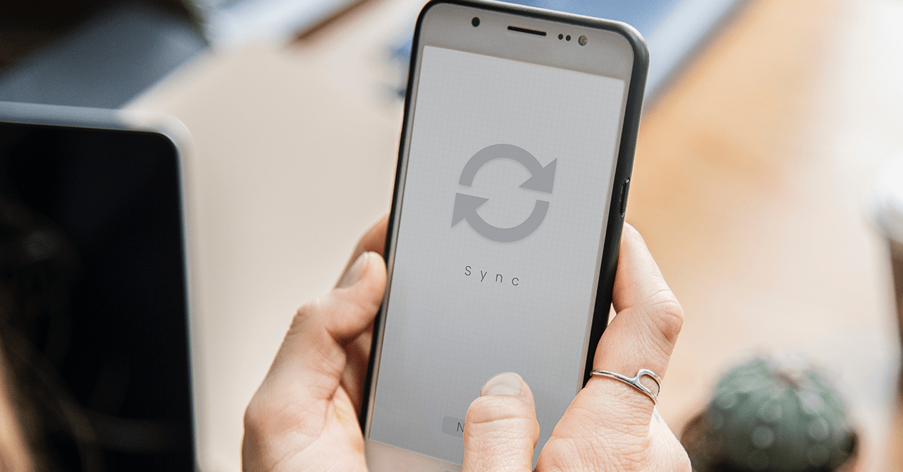 A person holds a phone with a sync symbol on the screen